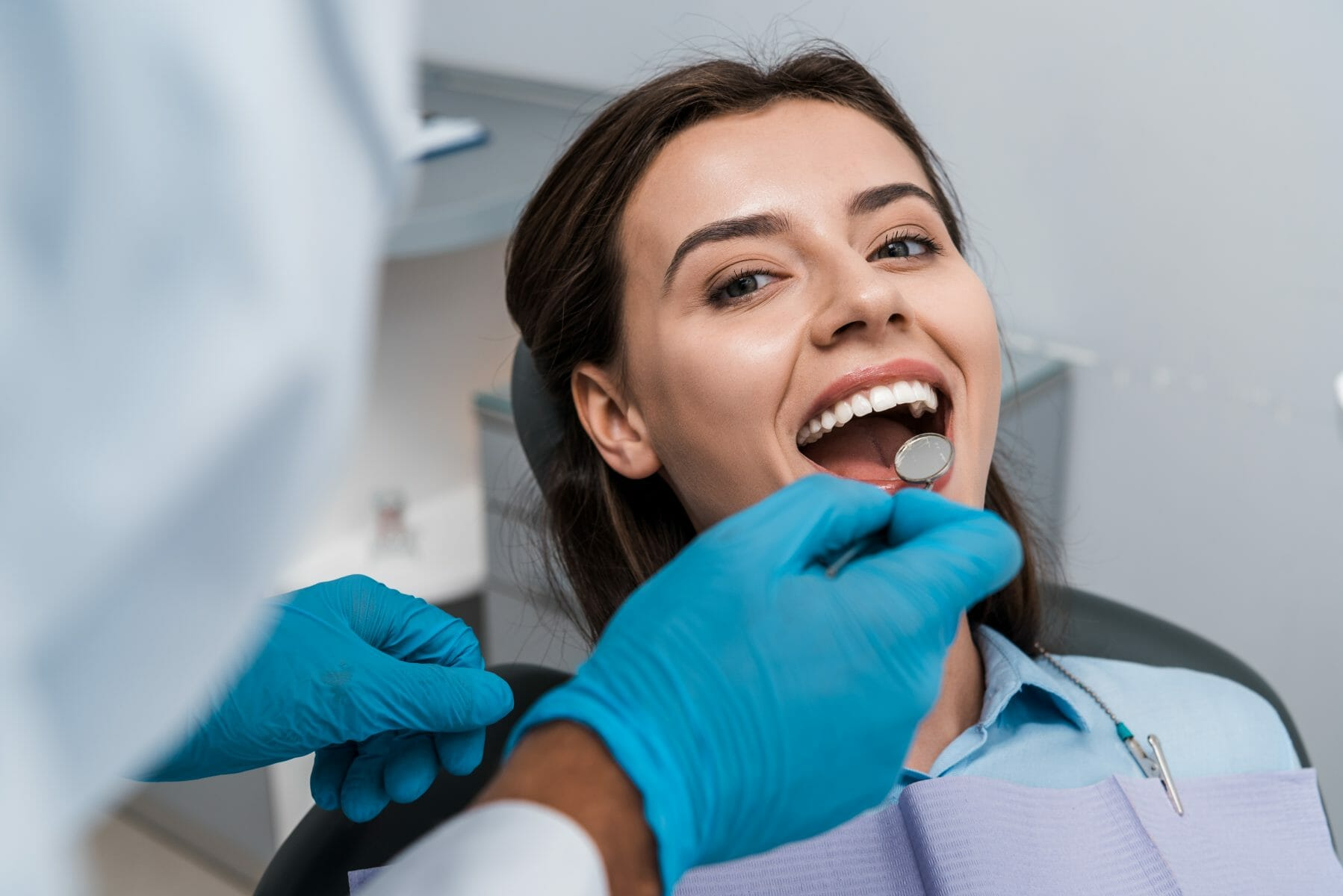 Dentist using mirror to see in patient mouth